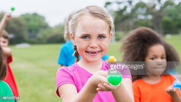 Little girl with freckles in an egg spoon race