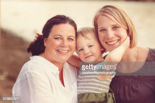 Little girl with her arms around both of her moms