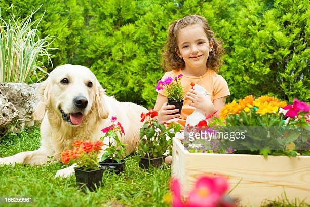 Little girl with her dog gardening.