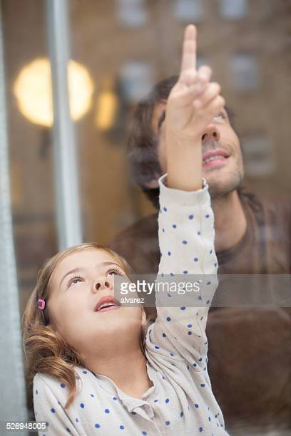 Little girl with her father looking outside window