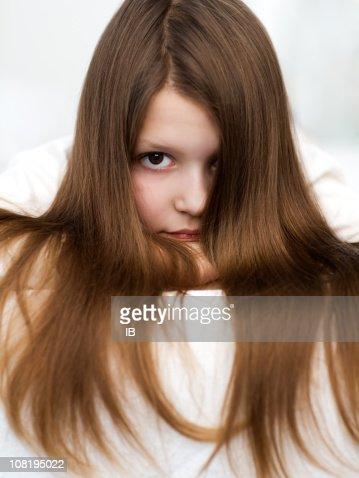 Petite fille avec de longs cheveux bruns Regarder fixement de l'avant face à la caméra