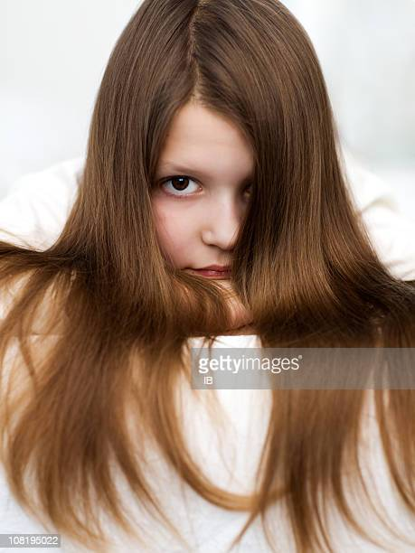 Little Girl with Long Brown Hair Staring Ahead Facing Camera