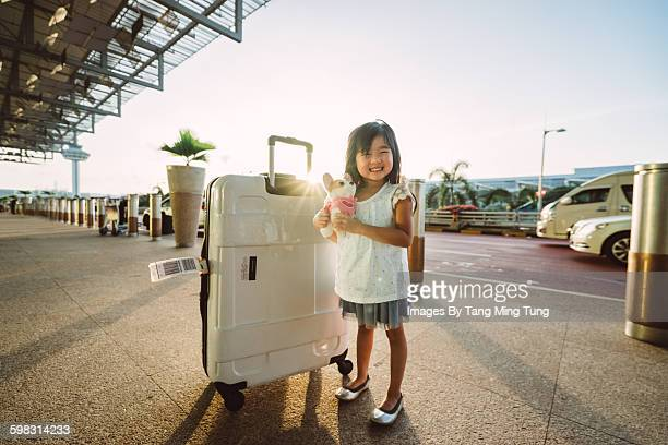 Little girl with luggage smiling joyfully at hotel