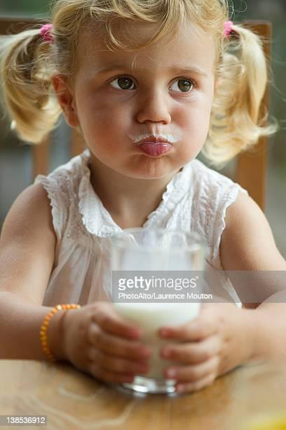 Little girl with milk mustache enjoying glass of milk