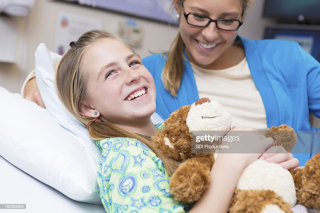 Little girl with mom and teddy bear in children's hospital : Stock Photo