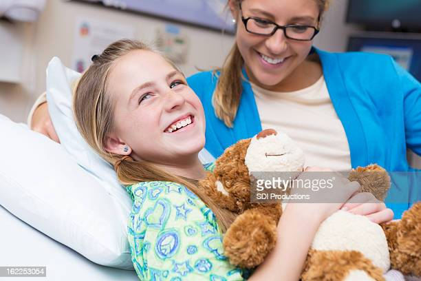 Little girl with mom and teddy bear in children's hospital