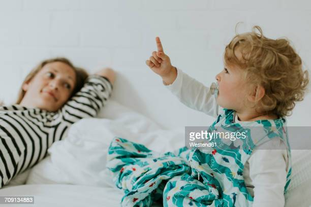 Little girl with mother in bed pointing her finger
