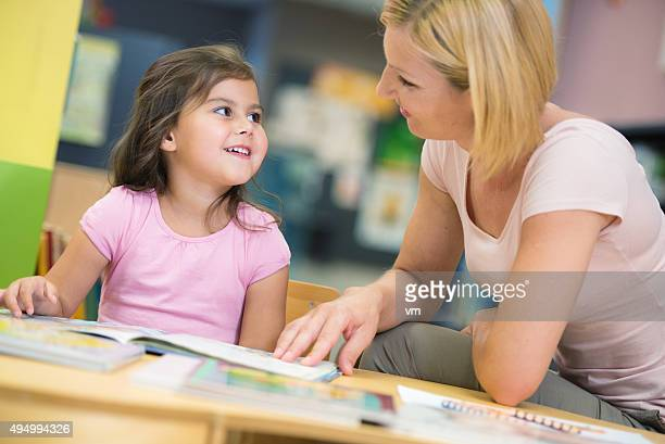Niña con la madre en la biblioteca
