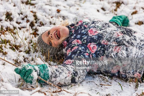 Little girl with outstretched tongue lying on snow covered meadow