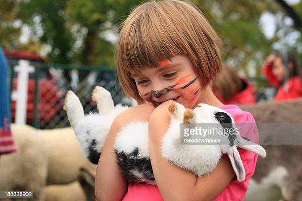 Little girl with painted tiger face holds rabbit upside down