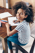 Little girl sitting at the kitchen table with pen and open notebook and looking at the camera