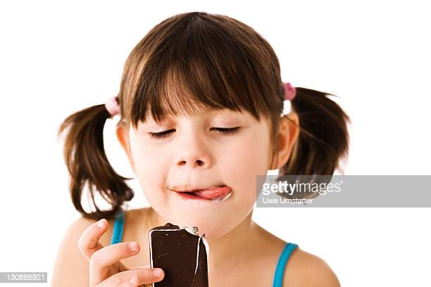 Little girl with pigtails eating ice cream