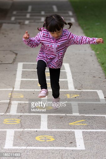 Little girl with pigtails playing hopscotch