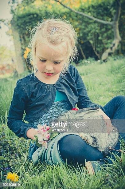 Little girl with rabbit sitting on meadow