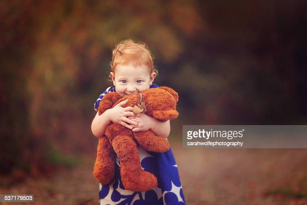 Little girl with red hair hugging a teddy bear