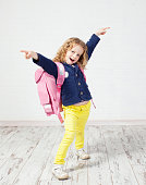 Little girl with schoolbag. Happy child at home