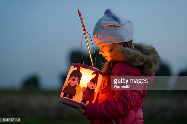 Little girl with self-made paper lantern in the evening