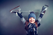 Cheerful little girl in warm sweater and hat holding figure skates.