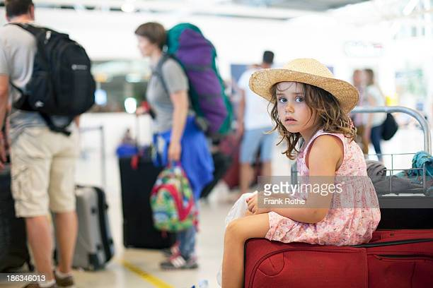 little girl with straw hat sitting at the airport