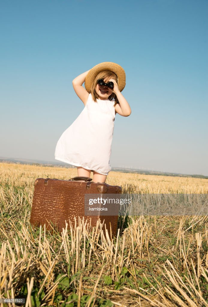 Little girl with suitcase is looking trough binoculars : Stockfoto