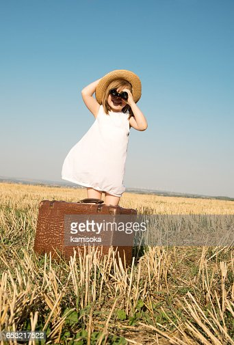 Little girl with suitcase is looking trough binoculars : Stock Photo