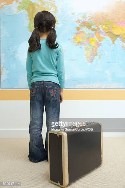 Little girl with suitcase looking at world map