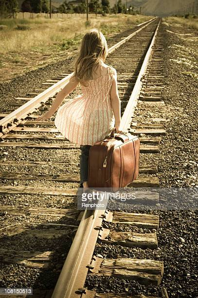 Little girl with suitcase walking down train tracks