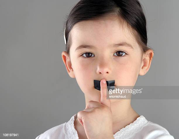 Little Girl with Tape Over Mouth Holding Finger to Lips
