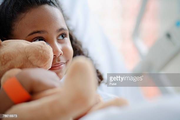 Little Girl with Teddy Bear in Hospital Bed