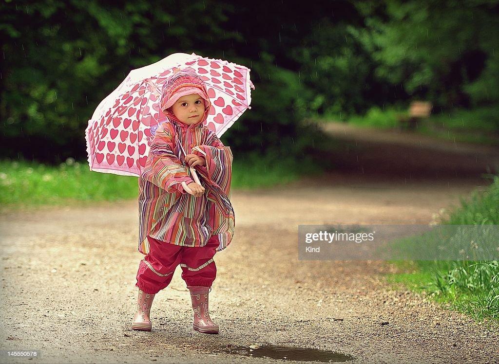 Little Girl With Umbrella In Rain Stock Photo