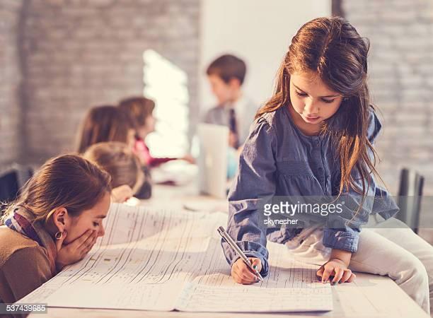 Little girl escribiendo plan de construcción.