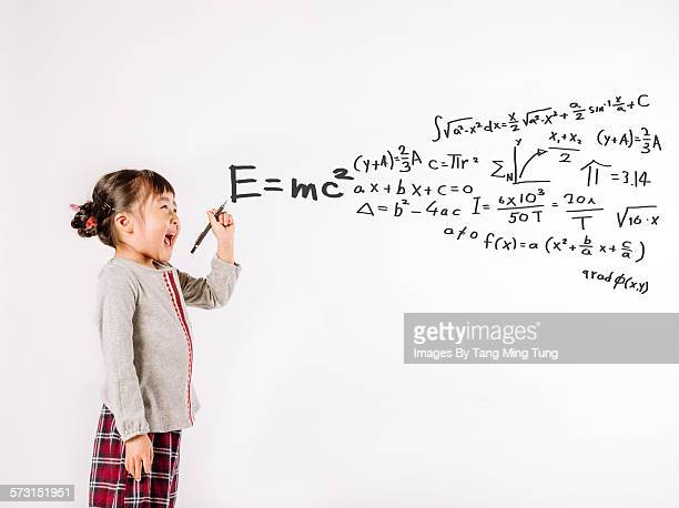 Little girl writing equations on white background