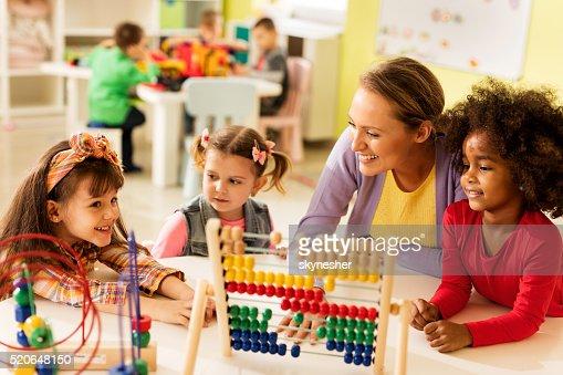 Little girls and teacher learning at preschool.