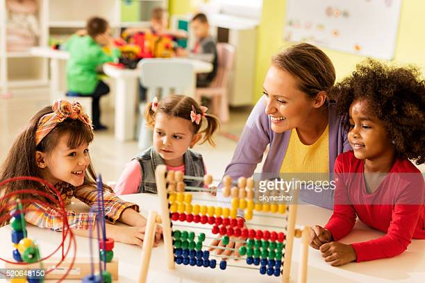 Little girls and teacher learning at preschool.