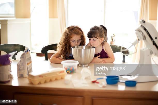 Niñas en mostrador de cocina con cocinar con ingredientes y herramientas