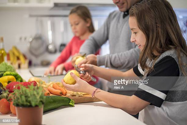Little girls cooking together with their father