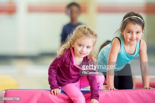 Little Girls Crawling Over Gym Mats