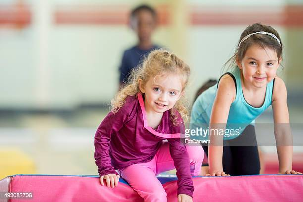 Little Girls Crawling Over Gym Mats