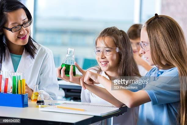Little girls doing chemistry experiment with teacher in classroom