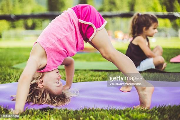 Kleine Mädchen tun yoga im park.