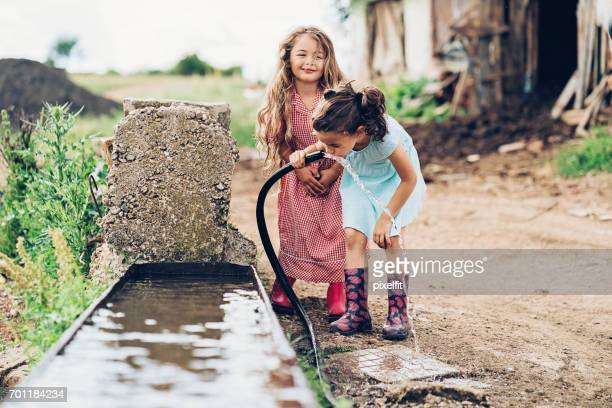 Little girls drinking water from a hose