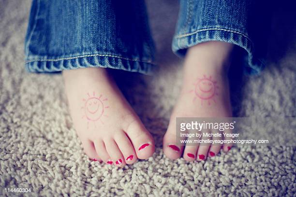 Little girls feet with painted toenails.