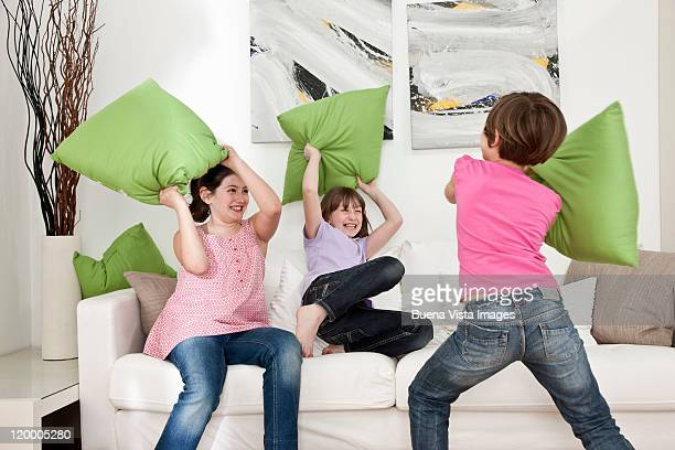 Little girls fighting with pillows