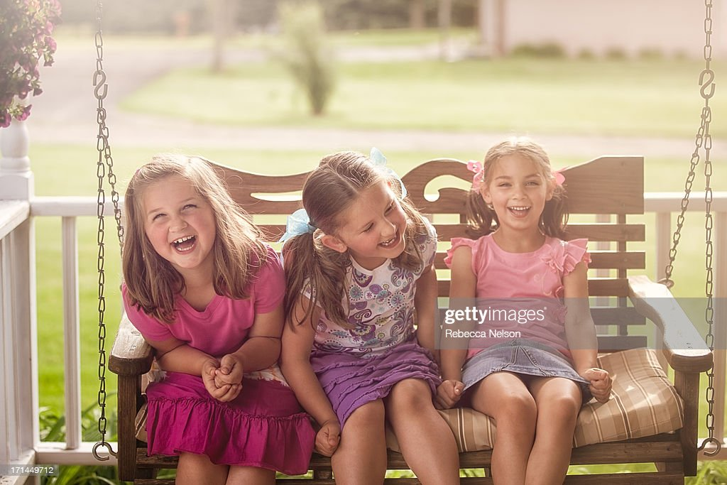 Little girls giggling on porch swing : Stock Photo