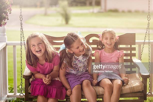 Little girls giggling on porch swing