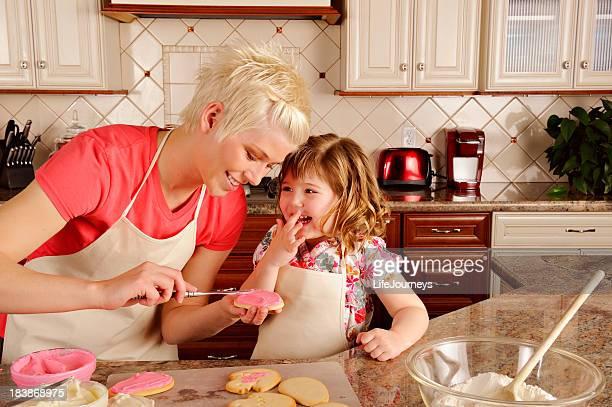 Schöne kleine Mädchen helfen Mommy-Kekse In der Küche