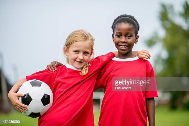 Niñas, que abrazan con una pelota de fútbol