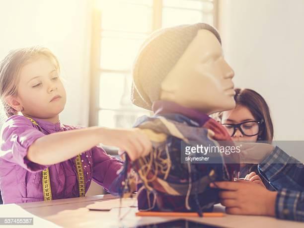 Little girls in clothing design studio.