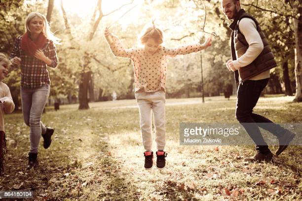 Little girls in park with parents playing with jump rope.