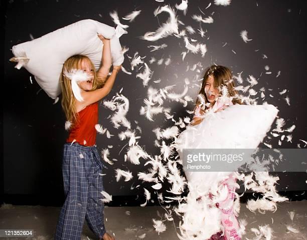 Kleine Mädchen kämpfen mit Kissen mit Federn überall